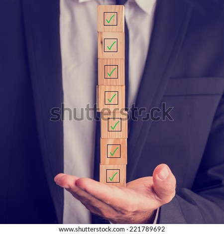 Businessman holding a stack of checked boxes marked on wooden cubes balanced on his hand conceptual of quality, completion, approval or voting. - stock photo