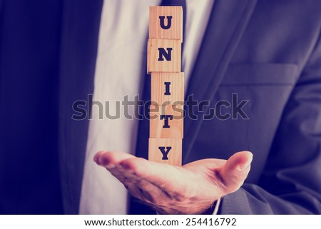Businessman holding a stack of five wooden cubes with the letters UNITY balanced on his palm, retro effect faded look. - stock photo