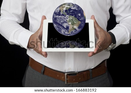 Businessman holding a tablet against black background and Earth  - stock photo