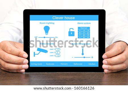 businessman holding a tablet computer with system clever house - stock photo