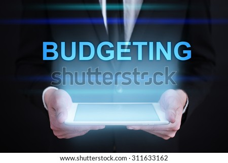 "Businessman holding a tablet pc with ""Budgeting"" text on virtual screen. Internet concept. Business concept."