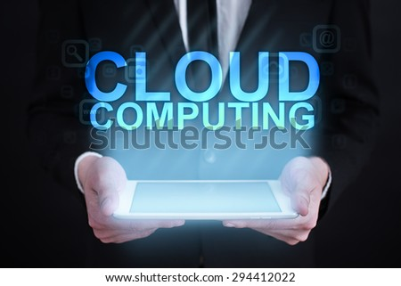 "Businessman holding a tablet pc with ""Cloud computing"" text on virtual screen. Internet concept. Business concept. - stock photo"