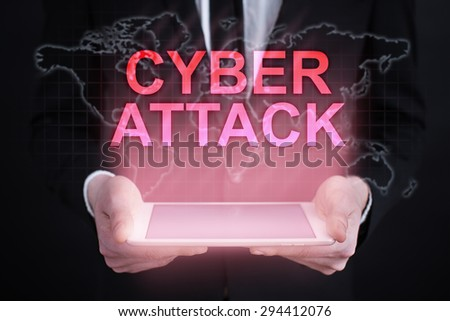 """Businessman holding a tablet pc with """"Cyber attack"""" text on virtual screen. Internet concept. Business concept. - stock photo"""
