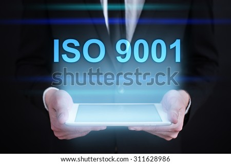 "Businessman holding a tablet pc with ""ISO 9001"" text on virtual screen. Internet concept. Business concept."