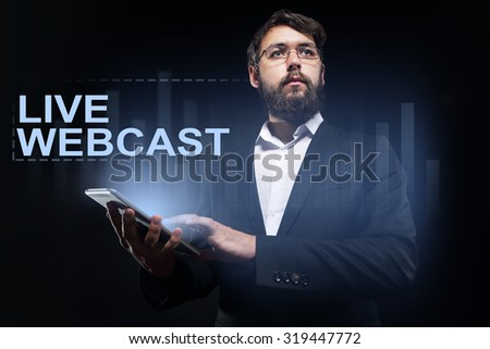 "Businessman holding a tablet pc with ""Live webcast"" text on virtual screen. - stock photo"