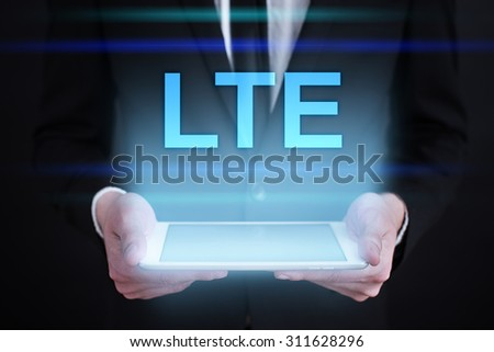 """Businessman holding a tablet pc with """"LTE"""" text on virtual screen. Internet concept. Business concept.  - stock photo"""
