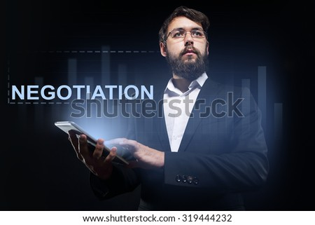 """Businessman holding a tablet pc with """"Negotiation"""" text on virtual screen. Business concept. - stock photo"""