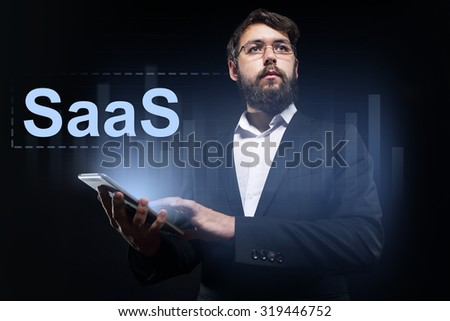 "Businessman holding a tablet pc with ""SaaS"" text on virtual screen."