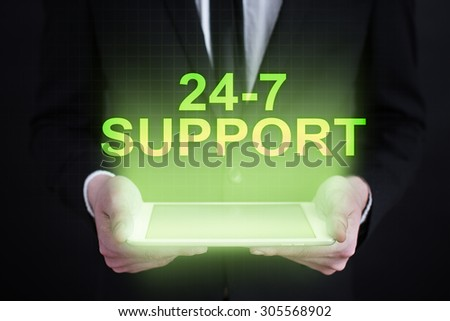 """Businessman holding a tablet pc with """"24-7 support"""" text on virtual screen. Business concept. Internet concept. - stock photo"""