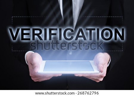 Businessman holding a tablet pc with verification text on virtual screen. Internet concept. Business concept. - stock photo