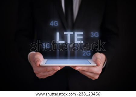 Businessman holding a tablet with a projected on-screen icon LTE. business concept. Internet concept. new communication technologies - stock photo