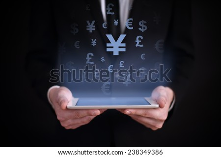 Businessman holding a tablet with a projected on-screen icon online trading yena. business concept. Internet concept.  - stock photo