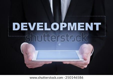 Businessman holding a tablet with development text on the screen. business concept. - stock photo