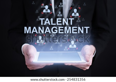 businessman holding a tablet with talent management concept on the screen. Internet concept. business concept. - stock photo