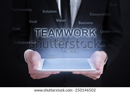 Businessman holding a tablet with teamwork words cloud on the screen. business  concept. - stock photo