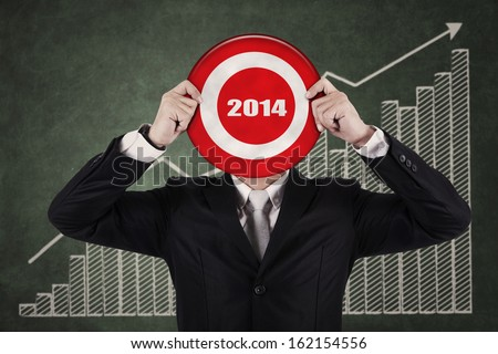 Businessman holding a target board with year 2014 writing in the middle - stock photo