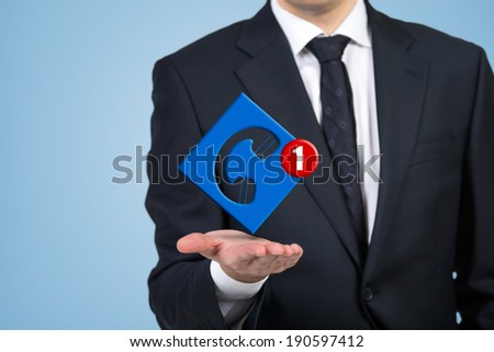 Businessman holding a 'telephone' icon - stock photo