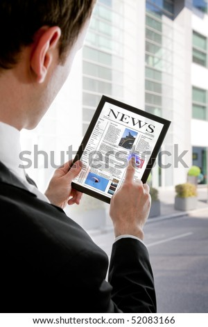 Businessman holding a touchpad pc and reading a newspaper - stock photo
