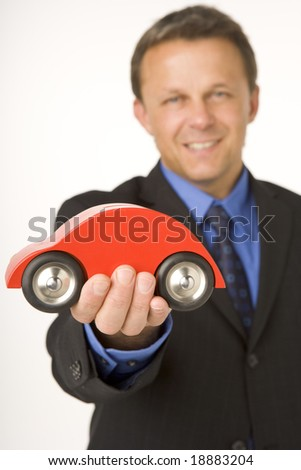 Businessman Holding A Toy Car - stock photo