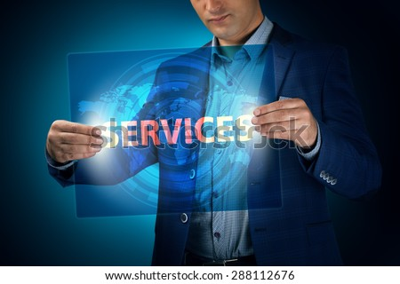 Businessman holding a transparent screen with an inscription a services. Business, technology, internet and networking concept. - stock photo