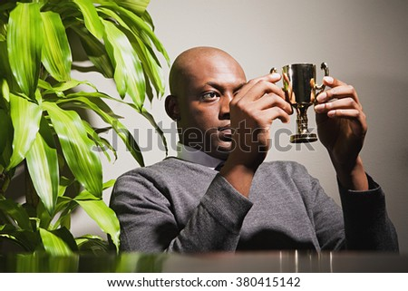 Businessman holding a trophy - stock photo
