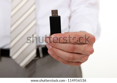 Businessman holding a USB stick - stock photo