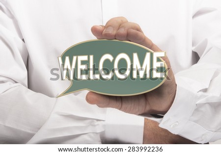 Businessman holding a welcome sign in left hand. Conceptual image