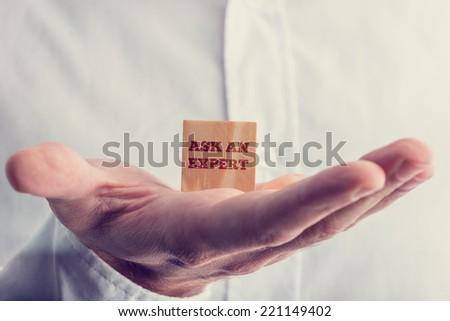 Businessman holding a wooden block reading - Ask an Expert - in the palm of his hand conceptual of consulting a professional, master or consultant for a solution and advice. - stock photo