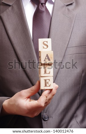 businessman holding a word sale made of wooden blocks - stock photo