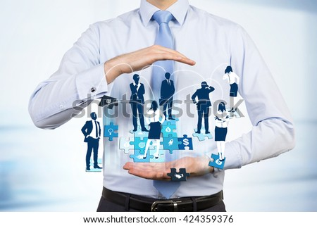 Businessman holding abstract image of businesspeople on puzzle pieces. Concept of teamwork and partnership - stock photo