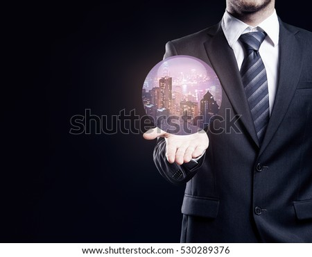 Businessman holding abstract sphere with city on dark background