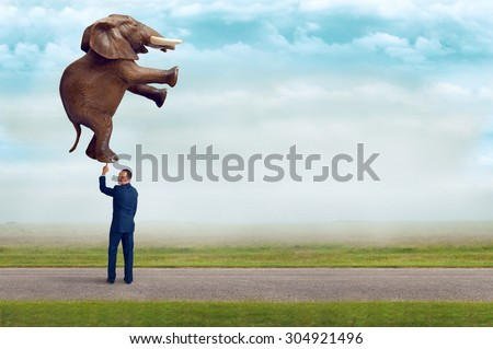 businessman holding an elephant with one finger subtle vintage filter and selective focus with copy space