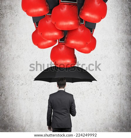 Businessman holding an umbrella protecting himself from falling boxing gloves. A metaphor of protection from crisis. - stock photo