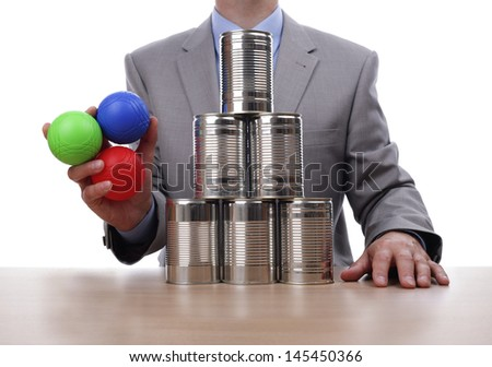 Businessman holding balls for tin can alley style business challenge concept for competition, chance, fortune or opportunity - stock photo