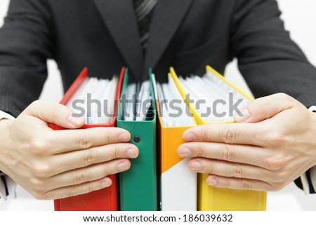 businessman holding binders at office - stock photo