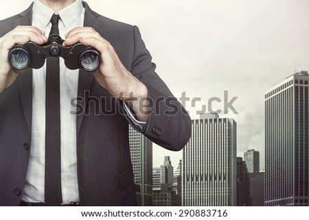 Businessman holding binoculars with tie and shirt on cityscape background - stock photo
