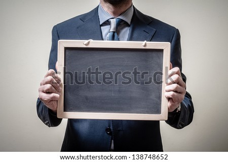 businessman holding blackboard on gray background