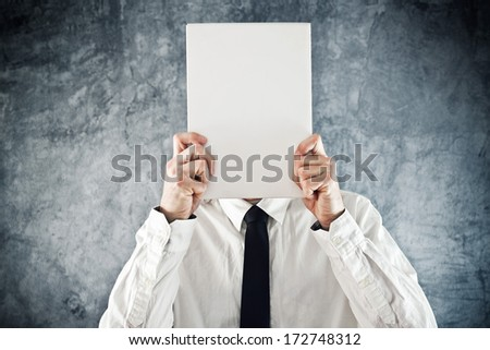 Businessman holding blank paper in front of his face with copy space for business message - stock photo