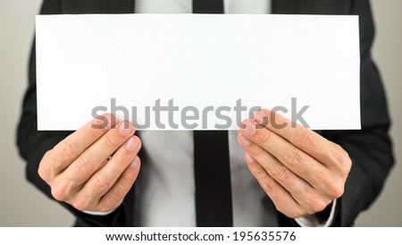 Businessman holding blank paper ready for your text or letters. - stock photo