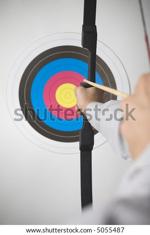 Businessman holding bow and shooting to archery target. Rear view, gray background - stock photo