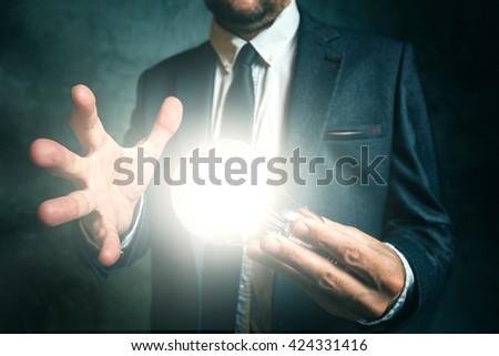 Businessman holding bright light bulb as metaphor of new ideas - stock photo
