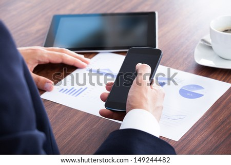 Businessman Holding Cell Phone And Analyzing Graph In Office - stock photo