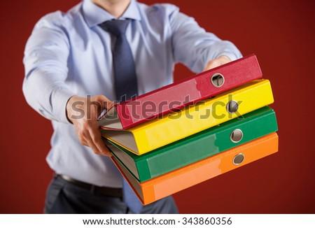 Businessman holding colored folders - stock photo