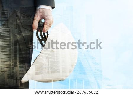Businessman holding construction helmet - stock photo