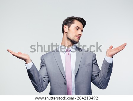 Businessman holding copyspace on the palms over gray background - stock photo