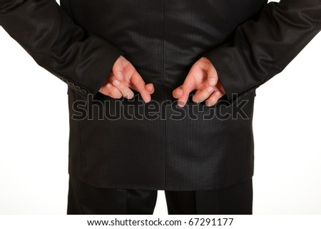 Businessman holding crossed fingers behind back isolated on white.  Close-up.