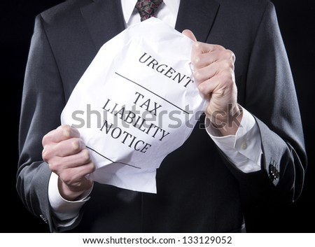 Businessman holding crumpled tax liability notice - stock photo