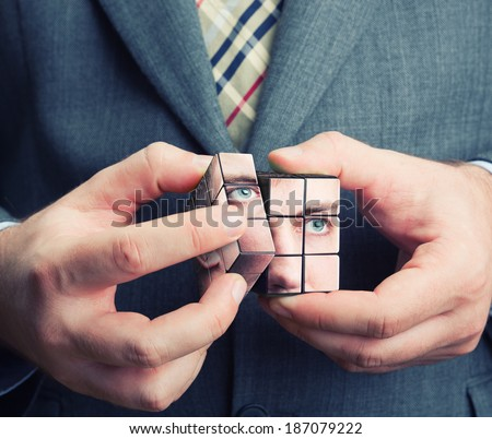 Businessman holding cube in his hands - stock photo