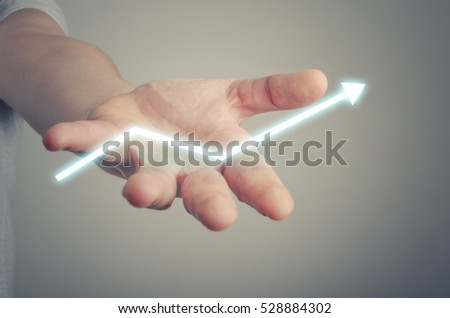 Businessman holding digital arrow in his hand