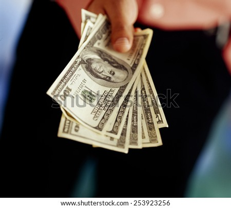 Businessman holding dollar - stock photo
